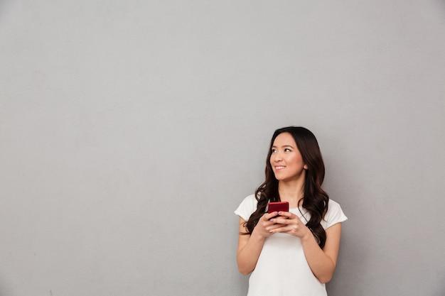 Молодая азиатская женщина в вскользь футболке беседуя или просматривая интернет на мобильном телефоне и смотря в сторону на copyspace, изолированном над серой стеной