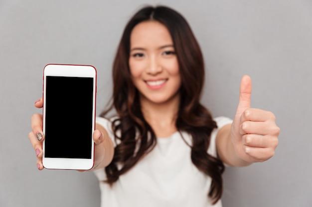 Изображение крупного плана китайской женщины в вскользь футболке представляя экран copyspace мобильного телефона и показывая большой палец руки вверх, изолированный над серой стеной