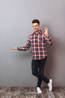 Полнометражное изображение улыбающегося человека в рубашке и джинсах держа copyspace на ладони и показывая одобренный знак пока смотрящ