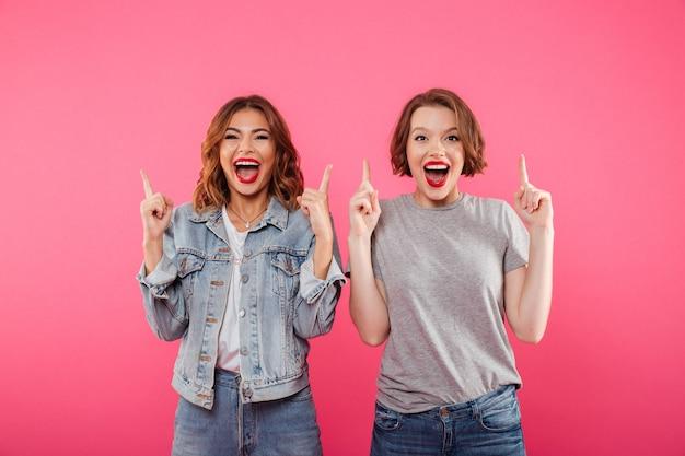Счастливые дамы друзья, указывая на copyspace.