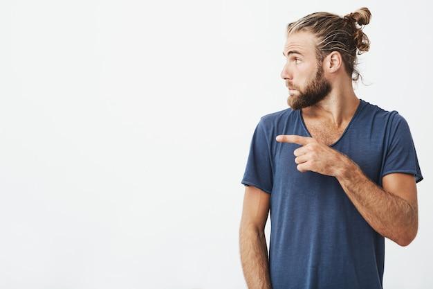 トレンディな散髪とひげの白いcopyspaceで彼の指を指しているプロファイルでうれしそうなハンサムな男の肖像画を間近します。