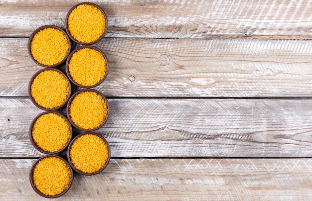 Желтая чечевица в коричневой миске плоской лежал на бежевом деревянном столе с copyspace