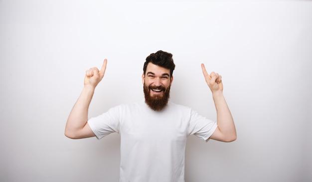 Фотография возбужденного улыбающегося человека с бородой в белой футболке, направленной вверх на copyspace