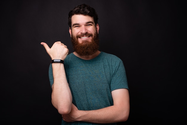 Фотография улыбающегося человека с бородой, указывая на copyspace