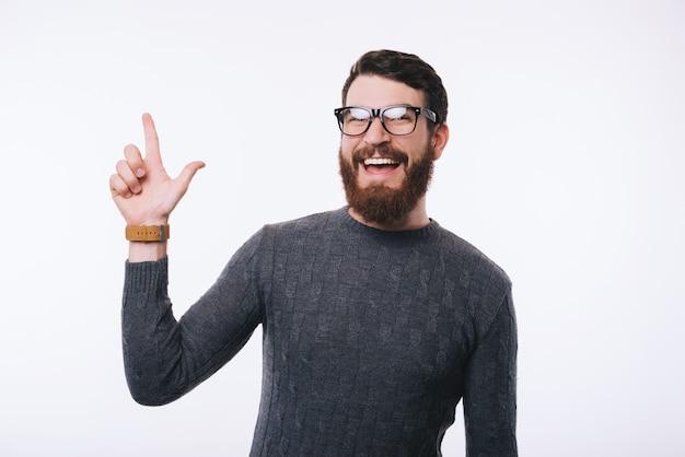 ひげの眼鏡を着用し、copyspaceをさして驚かれるハンサムな男