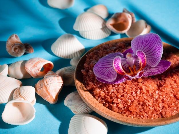 シェルと受け皿にオレンジのバスソルトと熱帯植物からの影で青い背景に花。 copyspace。スパ、リラックス、夏