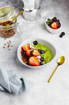 アボカド、バナナ、ほうれん草、グラノーラ入りココナッツミルク、ブルーベリー、ストロベリー、ココナッツチップのスモシーボウル。健康的な朝食のコンセプトです。免疫を高めるための食品。 copyspaceの平面図
