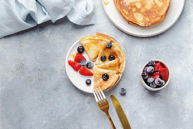 蜂蜜、イチゴ、ブルーベリーのクレープ、リネンナプキン、黄金の民俗とナイフとベリーと灰色の石の背景に焼かれた。 、薄いパンケーキ。健康的な朝食のコンセプトです。 copyspace付きフラットレイ