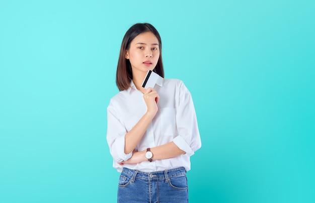 Привлекательная азиатская женщина держа оплату кредитной карточки с пересеченными оружиями против и смотря вперед на сини с copyspace.