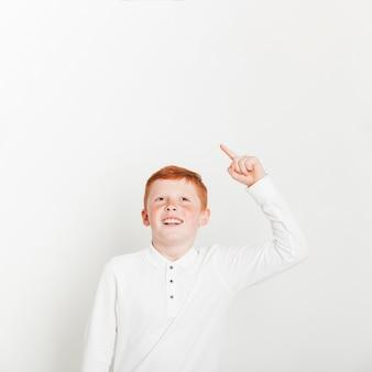 Рыжий мальчик, указывая на copyspace
