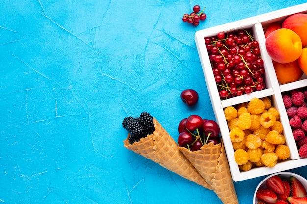 Плоская тарелка свежих ягод и фруктов с copyspace