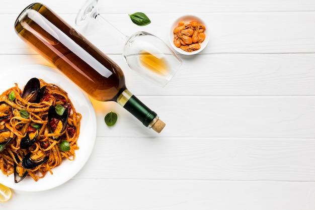 ムール貝のパスタとワインとcopyspaceの平らなプレート