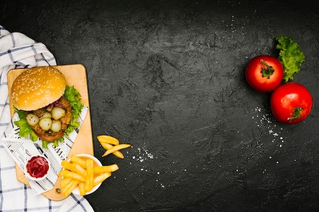 Плоский бургер и картофель фри на деревянной доске с copyspace