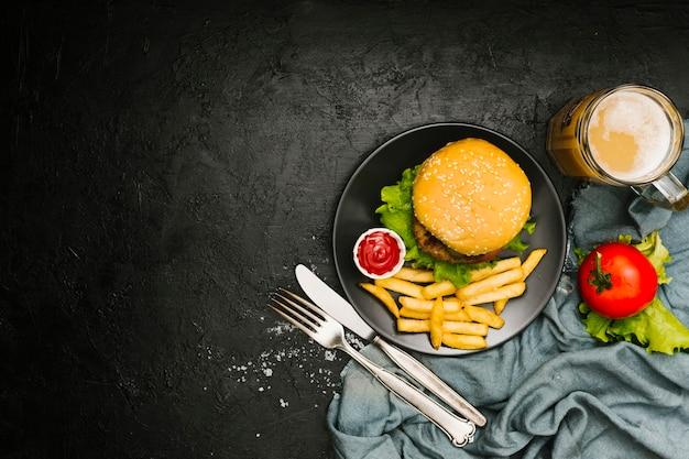Плоский бургер и картофель фри на тарелке с copyspace