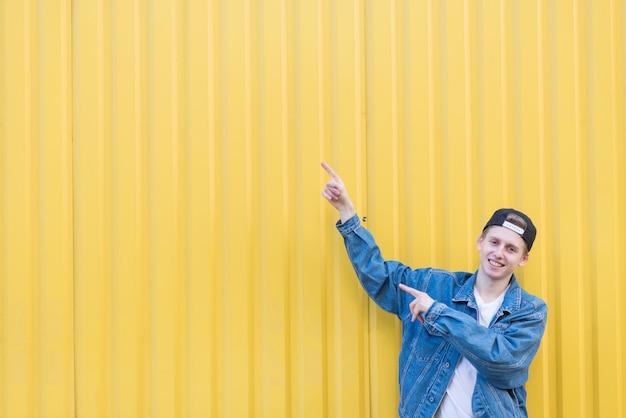 スタイリッシュな若い男が黄色の壁の上に立って、copyspaceの下の場所で彼の手を示しています