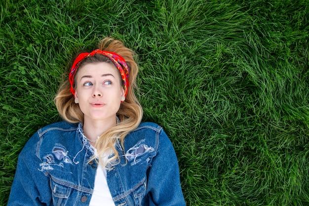 Смешная девчонка одета в джинсовой куртке, лежа на зеленой лужайке и глядя в сторону на copyspace. вид сверху.