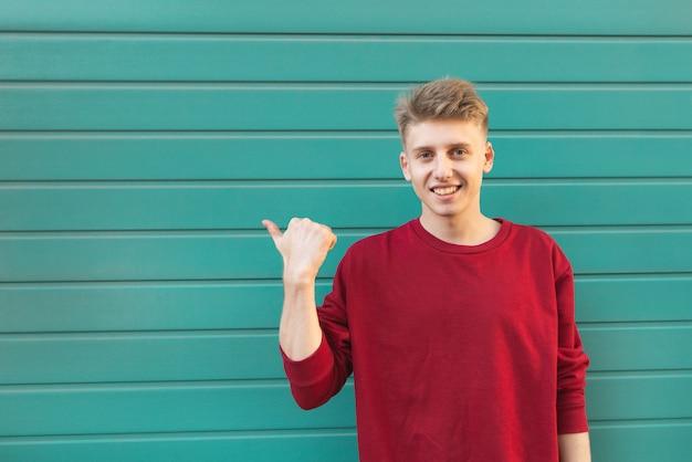 笑顔の若い男はcopyspaceに手を示しています。