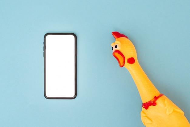 きしむような鶏のおもちゃが白い画面でスマートフォンを見て悲鳴を上げる。スマートフォン、おもちゃの鶏、copyspace