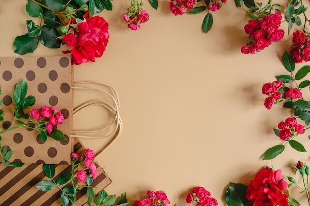 ハンドルの水玉とストライプとクラフトの背景に自然な赤いバラの包装袋。 copyspace付きフラットレイアウト