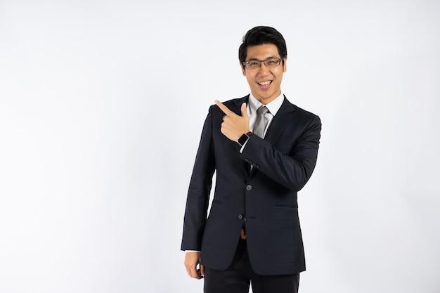 Умный азиатский бизнесмен в костюме указывая вверх для представления на copyspace против белой стены