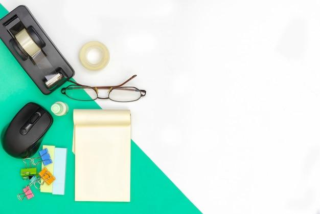 Современные офисные аксессуары на зеленой части бумаги на белом фоне с copyspace