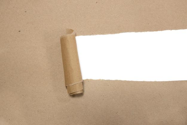 空白の白いcopyspaceと紙をロールアップした引き裂かれた茶色のパッケージ