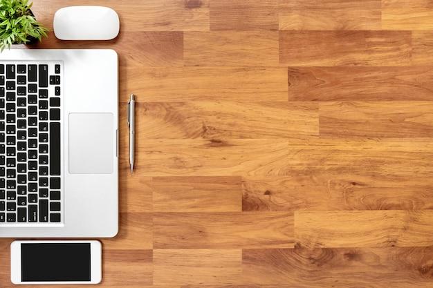 ラップトップコンピューター、スマートフォン、消耗品の木製オフィスデスクテーブル。トップビュー、copyspaceとフラットレイアウトの背景