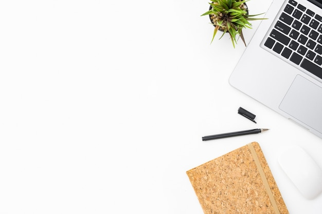 ラップトップコンピューターと事務用品の白い写真家の机。トップビュー、copyspaceとフラットレイアウトの背景
