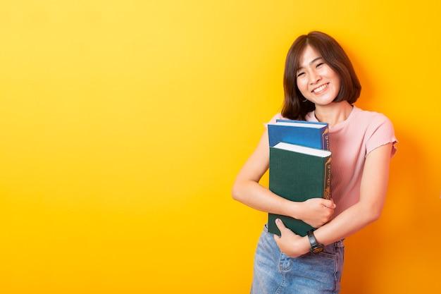 Copyspaceと黄色の壁に満足して美しいアジアの女性大学生