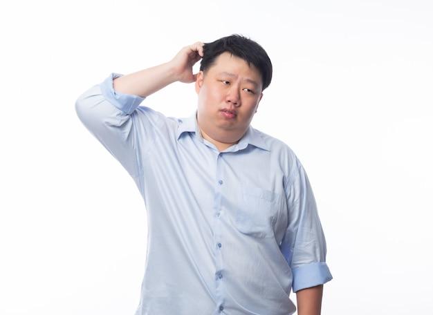 分離された疑いの顔とcopyspaceを探している青いシャツを着てアジアデブ男