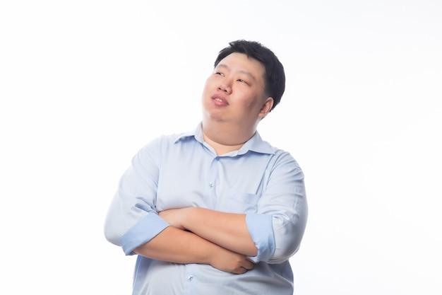 青いシャツの腕を組んで、分離された幸せそうな顔でcopyspaceを探しているアジアのデブ男