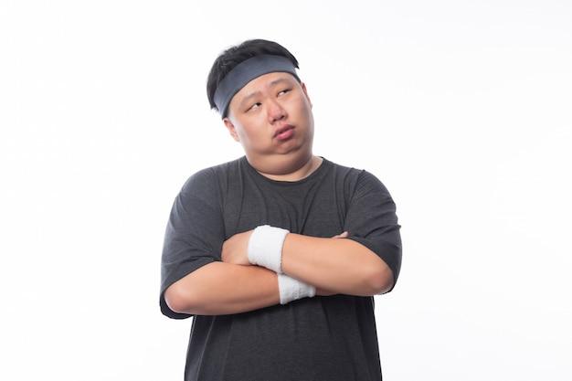 Азиатский смешной толстый человек в спортивной одежде пересек руку и смотрит на изолированное copyspace