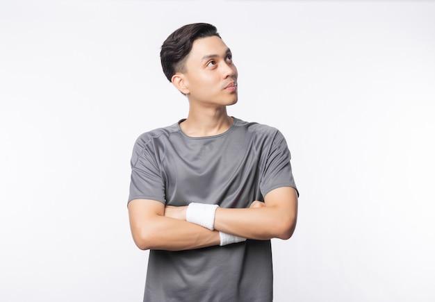 スポーツ服装の腕を組んで、白い壁に分離されたcopyspaceを探している若いアジア人