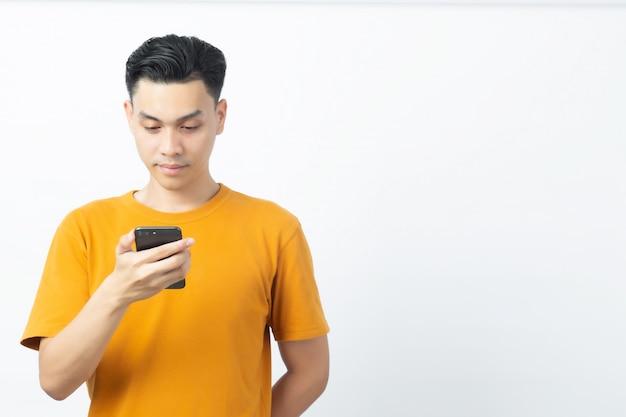白い背景のcopyspaceとスマートフォンからメッセージを読んで若い幸せなアジア人。