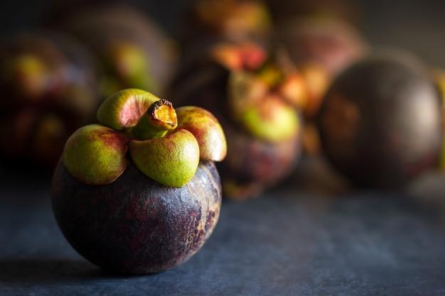 Плодоовощ мангустана на черном цементном поле и утреннем свете. является сезонным фруктом в таиланде. макрофотография и copyspace для текста.
