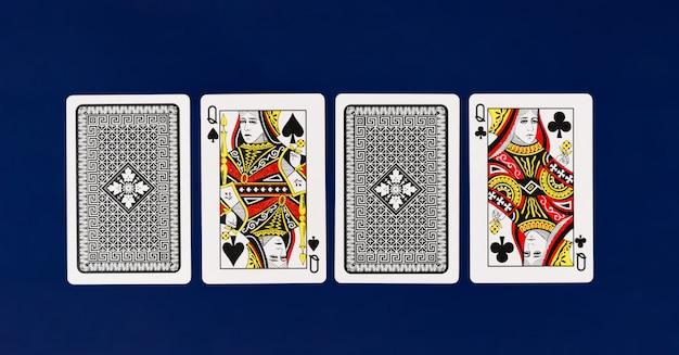 火かき棒およびカジノのcopyspaceのための無地の青い背景を持つ女王トランプ