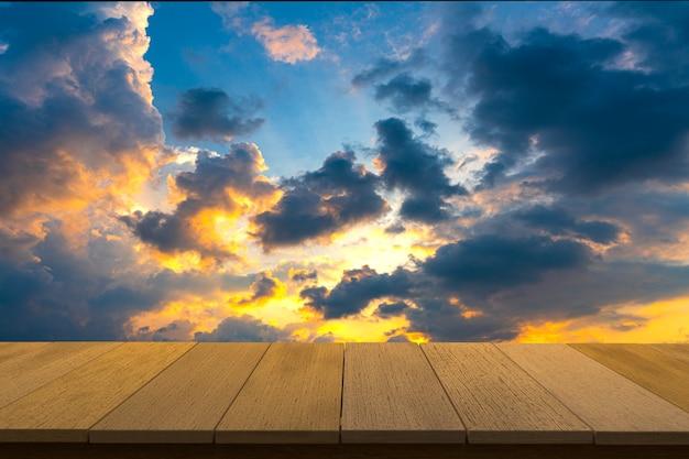 Деревянный стол с видом на закат небо фоне. вы можете использовать для отображения продуктов. copyspace.