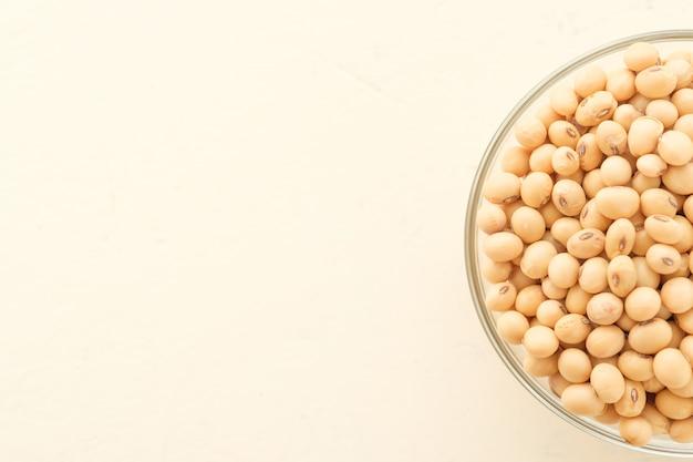 大豆はカップに入れられ、copyspace、ドライビーンイエローの木製テーブルの上に置かれます