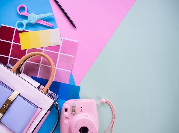 Композиция элементов женского графического дизайнера: цветовая схема, фотоаппарат, ножницы и цветная бумага с фоном copyspace