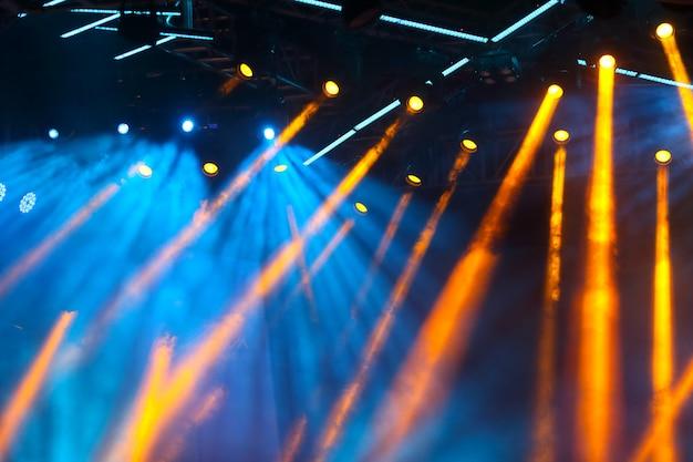 コンサートライトはcopyspaceと明るいステージの鮮やかな色の前に群がります