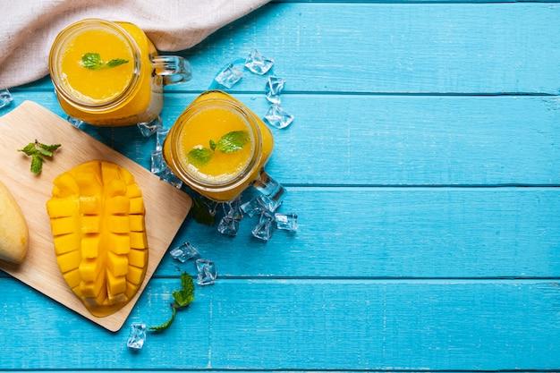 Освежающие манго смузи в стекле с спелых манго на деревянный стол и copyspace, вид сверху