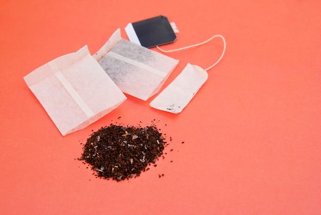 様々な種類のティーバッグをcopyspaceとピンクの紙。飲み物と飲み物。