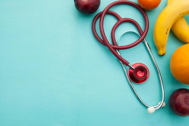 医学と医療、青の上の栄養医療保険。果物と赤いステトスコープ。 copyspace。