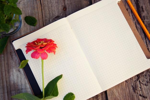 テキストの準備ができて。ピンクの花と古い木製のテーブルでノートブックを開きます。上面図。 copyspace。