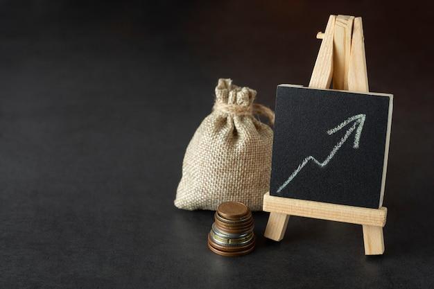 Финансовый. денежный мешок и нарисованная диаграмма. увеличение зарплаты или дохода. copyspace, темно.