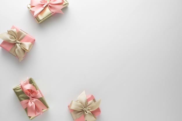 白地にピンクの弓リボンで美しい黄金の贈り物。クリスマス、パーティー、誕生日。シニーサプライズボックスcopyspaceを祝います。創造的なフラットレイアウトトップビュー。