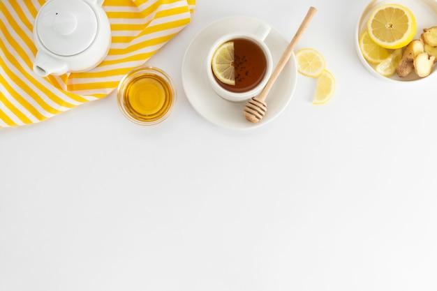 白にレモンと蜂蜜入りの紅茶。ホットティーカップが分離された、平面図フラットレイアウト。フラット横たわっていた。秋、秋、冬の飲み物。 copyspace。
