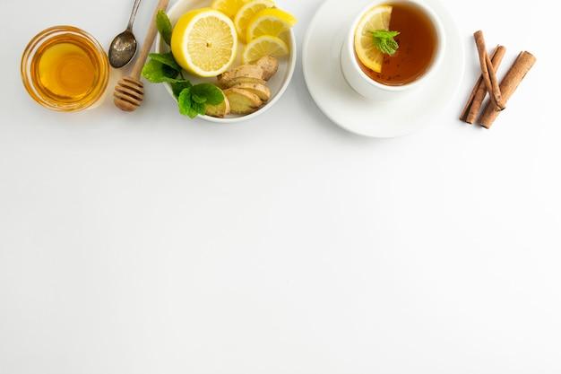 白地にレモンと蜂蜜入りの新鮮なお茶。ホットティーカップが分離された、平面図フラットレイアウト。フラット横たわっていた。秋、秋、冬の飲み物。 copyspace。