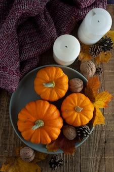 秋、プレートの素朴な木製の背景にオレンジ色のカボチャと秋の感謝祭フラットレイアウトcopyspace