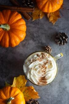Copyspace秋の飲み物とシナモンとクリームの泡トップビューでスパイスの秋のカボチャラテドリンク